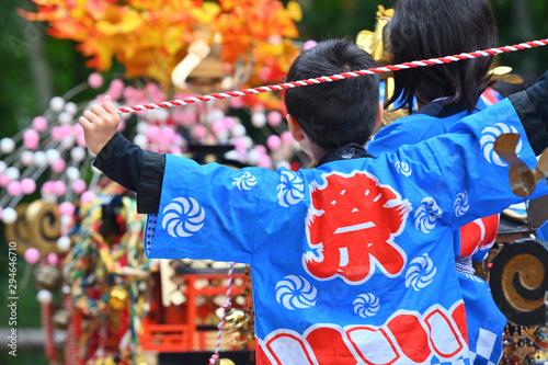 祭りの法被を着た少年とお御輿