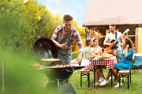 Group of friends at barbecue party outdoors. Young man near grill Fotobehang