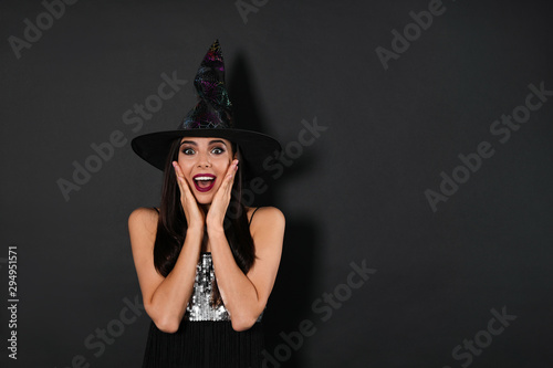 Fényképezés Excited woman wearing witch costume for Halloween party on black background, spa