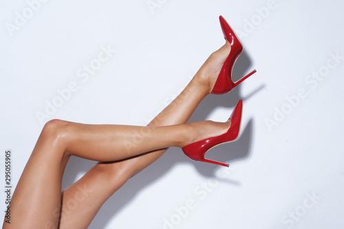 Obraz na plátně Isolated female legs in red high heels. Studio shoot.
