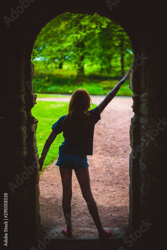 Photo Silhouette of a Girl Leaving a Stone Archway Going into Nature