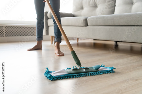 Obraz na płótnie Woman housewife holding mop cleaning floor at home, close up