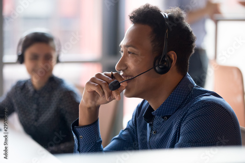 Fotografia Smiling young african businessman call center agent laugh at workplace