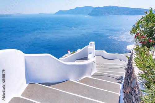Fototapeta premium Tradycyjna wąska ulica ze schodami prowadzącymi do morza w miejscowości Oia, wyspa Santorini, Grecja. Piękny letni krajobraz, widok na morze