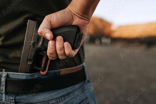 Obraz na płótnie Man holding hidden short gun in his hand.