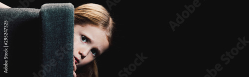 Canvas panoramic shot of scared child looking at camera while hiding behind armchair is