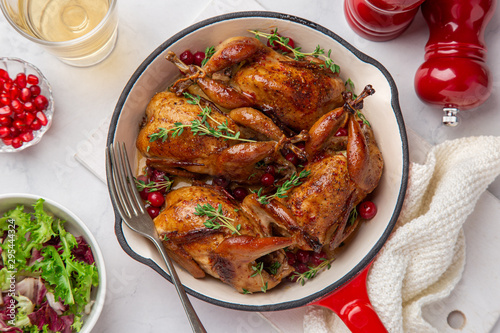 Fotografia Roasted quail with cranberry and thyme on pan