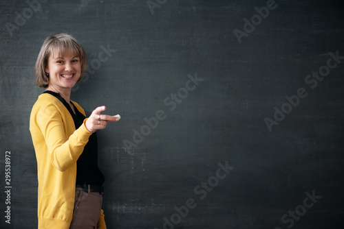 Canvas Print Young teacher with piece of chalk is standing near blackboard in a classroom