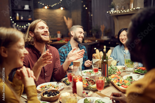 Wallpaper Mural Group of emotional young people enjoying dinner party with friends and smiling h