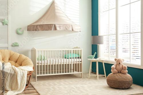 Tapete Cute nursery interior with comfortable crib near white wall