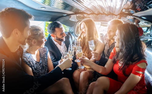 Photo Group of women and men clinking glasses in a limousine