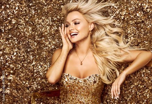 Beautiful blonde woman in golden flowers garden Fototapete
