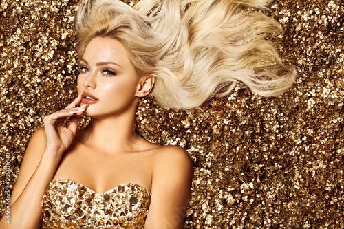 Piękna blondynki kobieta w złotym kwiatu ogródzie
