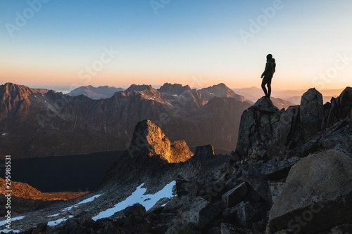 Photo Horizontal shot of a male fearlessly standing on the top of a cliff enjoying the