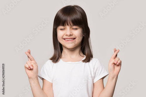 Foto Smiling small girl cross fingers making wish