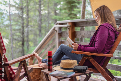 Fotografija woman sitting outside cabin in woods relaxing with a book