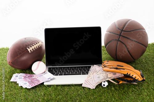 Canvas laptop near sports balls, baseball glove, euro and dollar banknotes on green gra