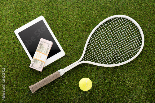 Foto top view of tennis racket and ball near digital tablet and euro banknotes on gre