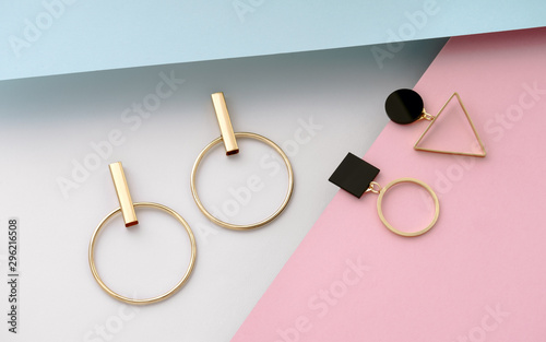 Leinwand Poster Two pairs of geometric shape golden earrings on pastel colors background