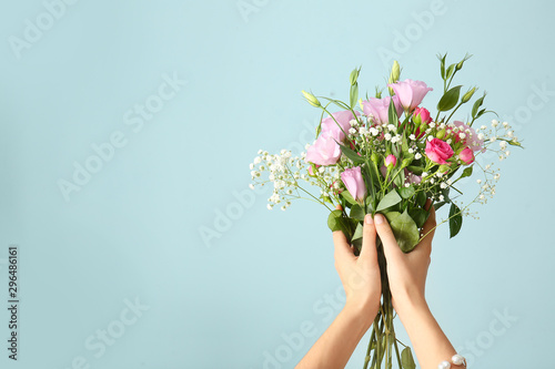 Leinwand Poster Female hands with bouquet of beautiful flowers on color background