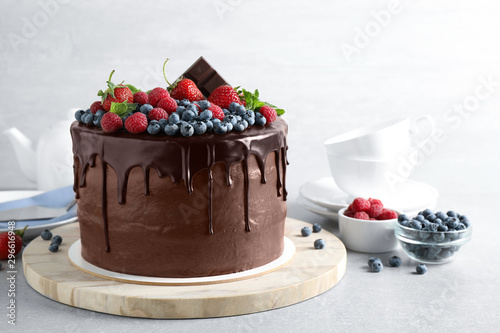 Foto Freshly made delicious chocolate cake decorated with berries on white table