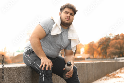 Young overweight man with towel resting in park