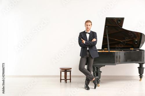 Fotografie, Obraz Man near grand piano against white wall