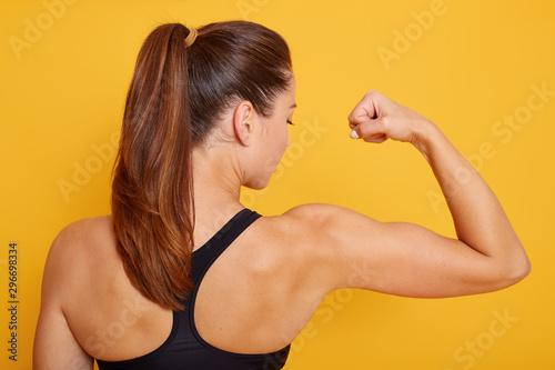 Horizontal shot of attractive fitness woman posing backwards isolated over yellow studio background Fotobehang