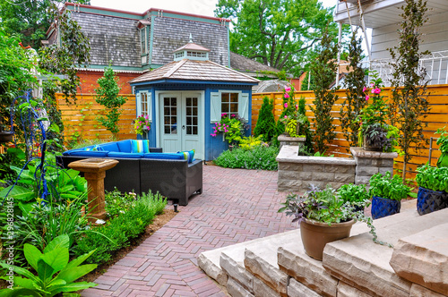 Obraz na płótnie Contemporary with traditional elements, this beautiful small urban backyard garden features a seat wall, red brick paver herringbone patio, high end shed,  and mixed planting for colour and privacy