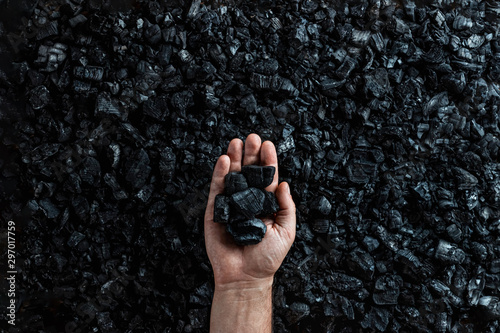 Canvas Print Male hand with coal on the background of a heap of coal, coal mining in an open pit quarry, copy space