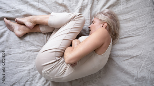 Fotografie, Obraz Depressed mature woman lying alone on bed in fetal position
