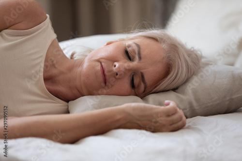Fotografia, Obraz Calm serene older woman sleeping alone in bed, closeup view