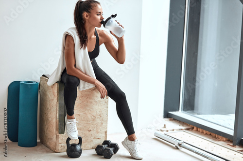 Cuadros en Lienzo Young woman in leggins with towel on shoulders drinking water after fitness trai