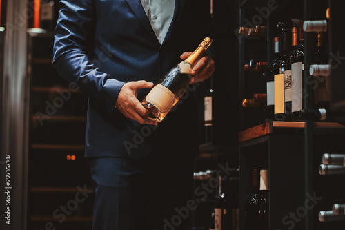 Canvas Print Elegant man in suit at wine cellar with bottle of wine