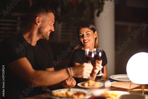 Fototapeta Young beautiful couple dinning on celebration toasting and smiling at terrace