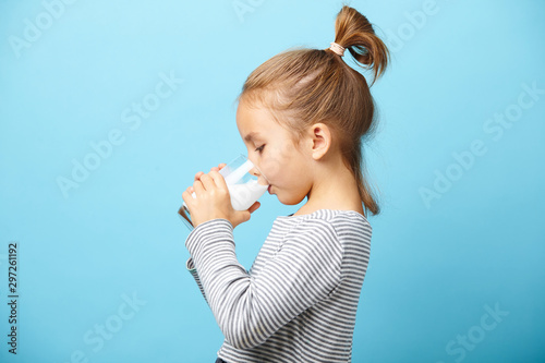 Fotografia Child girl drinks milk without lactose, sideways portrait against blue isolated