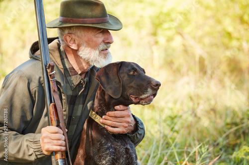 Fotografia, Obraz Caucasian mature man with gun and dog sit searching prey