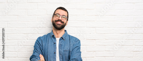 Fotografia Handsome man with beard over white brick wall with glasses and happy