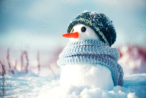 Canvas Print Little cute snowman in a knitted hat and scarf on snow on a sunny winter day