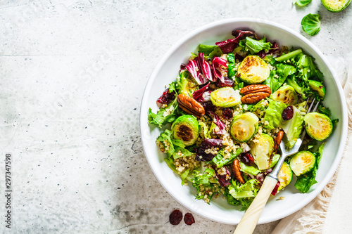 Canvas Print Fried brussels sprouts salad with quinoa, cranberries and nuts in white bowl, top view