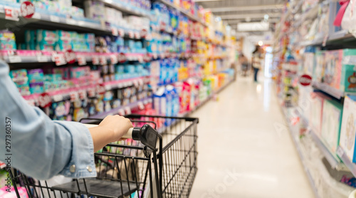 shopping in a supermarket concept.Shopping in supermarket a shopping cart view with motion blur.Close up of a woman shopping in a supermarket.Customer pushing a shopping cart in a supermarket.