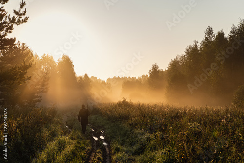 Obraz na płótnie Bird Hunter at Sunrise going for hunt in a forest with his shotgun rifle