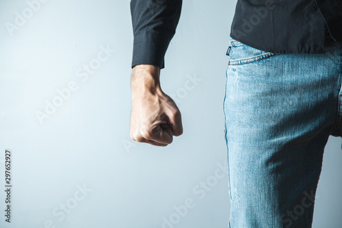 Murais de parede angry man fist on gray wall background
