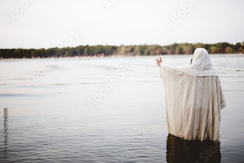 Fototapeta Person wearing a biblical robe standing in the water with a hand up
