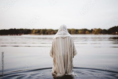 Fotografie, Obraz Person wearing a biblical robe walking in the water with a blurred background sh