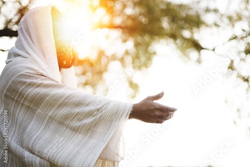 Fotografija Biblical scene - of Jesus Christ landing a hand for help with the sun shining ne