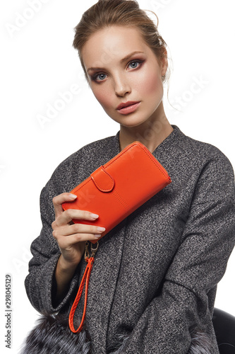 Valokuvatapetti Medium close-up shot of a young brown-haired European lady in a gray mottled jacket with a textured orange leather wallet with a buckle opening closure and a wristlet strap handle in her hand