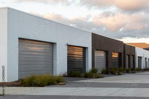 Obraz na plátně Modern car garages reflecting golden afternoon light in suburban area