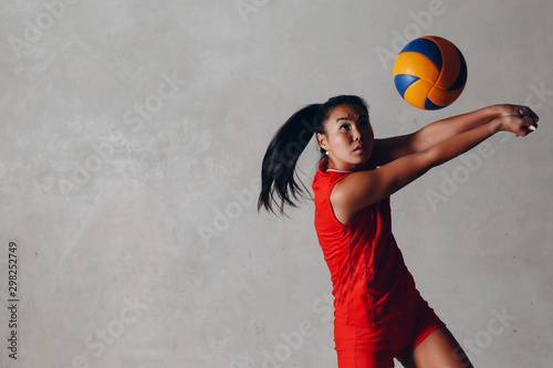 Young Asian woman volleyball player in red uniform takes ball