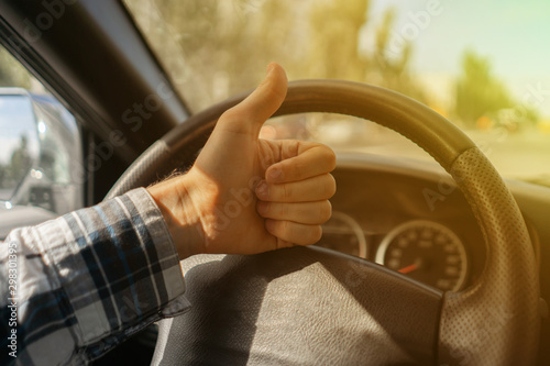 Canvas Print first person view of driver showing thumb up in front of steering wheel